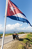 the cuban flag flying at the snorkeling snack bar La Batea, horse-drawn carriage on a lonely coast road from La Boca to Playa Ancon, with beautiful small beaches in between, at the beach, turquoise blue sea, family travel to Cuba, parental leave, holiday,