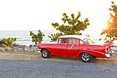 red oldtimer on a lonely coast road from La Boca to Playa Ancon, with beautiful small beaches in between,  turquoise blue sea, family travel to Cuba, parental leave, holiday, time-out, adventure, near Trinidad, Cuba, Caribbean island