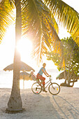 family on a bicycle tour, palm tree, mother with child cycling, lonely coast road from La Boca to Playa Ancon, with beautiful small sandy beaches in between, at the beach, turquoise blue sea, family travel to Cuba, parental leave, holiday, time-out, adven