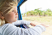 girl looking out of the window, hair blowing in the wind, on the way from Cayo Coco to Santa Clara, on the road, empty street, no traffic, horse-drawn carriage, horse, transport, oldtimer, blue, family travel to Cuba, parental leave, holiday, time-out, ad