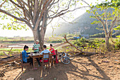 Friends playing cards at a table next to fields, Mogotes and tobacco fields in Vinales, climbing region, loneliness, beautiful nature, family travel to Cuba, parental leave, holiday, time-out, adventure, National Park Vinales, Vinales, Pinar del Rio, Cuba