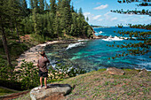 A young man enjoys a cigarette and a beautiful view above one of Norfolk Island's many popular coves, Norfolk Island, Australia