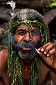 A local man with beard and leafy headdress smokes a self-made cigarette, Waisisi Bay, Tanna Island, Vanuatu, South Pacific