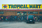 Many people stand under an awning at the Tropical Mart to avoid heavy rain, Rabaul, East New Britain, Papua New Guinea, South Pacific