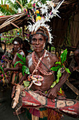 A man in traditional dress and headdress holds a drum and smiles during a cultural performance, Kopar, East Sepik, Papua New Guinea, South Pacific