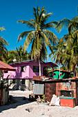 Ein bunt bemaltes zweistöckiges Holzhaus steht in Kontrast zu einer Wellblechhütte in einem Fischerdorf auf Pulau Mantanani, Mantanani-Inseln, nahe Sabah, Malaysia, Asien