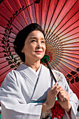 A middle-aged Japanese woman wearing a kimono and holding a parasol looks into the distance, Kanazawa, Ishikawa, Japan, Asia