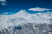 Aerial of Koryaksky volcano and trees in snow-covered landscape near Petropavlovsk taken through window of helicopter, near Petropavlovsk-Kamchatsky, Kamchatka, Russia, Asia