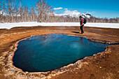 A tour guide walks around one of the hot springs in Nalychevo National Park, near Petropavlovsk-Kamchatsky, Kamchatka, Russia, Asia