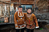 Two smiling young men in traditional Itelmen dress stand in front of a private home, Itelmen Homestead, Kamchatka, Russia, Asia