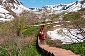 A group of German tourists walks on a boardwalk through the Valley of Geysers (UNESCO World Heritage Site), near Petropavlovsk-Kamchatsky, Kamchatka, Russia, Asia