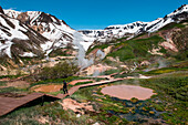 A German tourist walks on a boardwalk amidst steaming pools of water in the Valley of Geysers (UNESCO World Heritage Site), near Petropavlovsk-Kamchatsky, Kamchatka, Russia, Asia