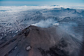 Aerial of the Karymsky Volcano (Stratovolcano) with steam rising from its caldera seen from helicopter, near Petropavlovsk-Kamchatsky, Kamchatka, Russia, Asia