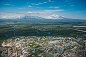 Aerial of suburbs outside Petropavlovsk-Kamchatsky with volcanic mountains in the background seen from helicopter, Petropavlovsk-Kamchatsky, Kamchatka, Russia, Asia