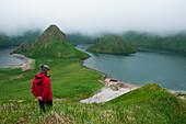 A tourist in red parka stands in high grass above the water-filled caldera, Yankicha Island, Uschischir, Kuril Islands, Sea of Okhotsk, Russia, Asia