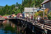 Touristen laufen entlang der Creek Street, gebaut über dem Gewässer von Ketchikan Creek, Ketchikan, Alaska, USA, Nordamerika