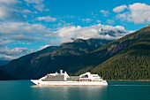 Cruise ship Seabourn Sojourn (Seabourn Cruise Line) passes by forested snow-dusted mountains, Prince Frederick Sound, Alaska, USA, North America