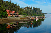 Calm weather creates a near-perfect mirror image of a large house, a pier, and a small boat on a forested peninsula, Elfin Cove, Chichagof Island, Alaska, USA, North America