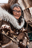 An elderly woman with glasses and traditional fur clothing sits in front of a reindeer-fur teepee, Gjoa Haven, King William Island, Nunavut, Canada, North America