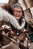 Eine ältere Frau mit Brille und traditioneller Pelzkleidung sitzt vor einem Tipi Zelt aus Rentierfell, Gjoa Haven, King William Island, Nunavut, Kanada, Nordamerika