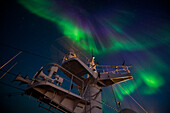 The northern lights (also polar lights or Aurora Borealis) light up the sky just after sunset, seen from aboard expedition cruise ship MS Bremen (Hapag-Lloyd Cruises), between Northeast Cape and Cape Ossory, Nunavut, northern Canada, North America