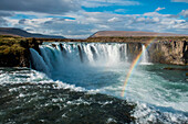 A bright rainbow spreads over 12 meter high Goðafoss (Waterfall of the Gods), near Seyðisfjörðdur, Eastern Iceland, Europe