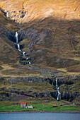 Farm buildings are dwarfed by a multiple waterfall in the steep landscape bordering Seyðisfjörðdur fjord, near Seyðisfjörðdur, Eastern Iceland, Europe