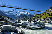 Person crossing Hooker River on suspension bridge, Hooker valley, Mount Cook, Mount Cook National Park, UNESCO Welterbe Te Wahipounamu, Lake Pukaki, Canterbury, South island, New Zealand