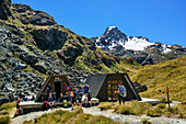 Several persons standing in front of shelter huts at Harris Saddle, Routeburn Track, Great Walks, Fiordland National Park, UNESCO Welterbe Te Wahipounamu, Queenstown-Lake District, Otago, South island, New Zealand