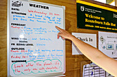 Person pointing at signboard with weather forecast, Routeburn Falls Hut, Routeburn Track, Great Walks, Fiordland National Park, UNESCO Welterbe Te Wahipounamu, Queenstown-Lake District, Otago, South island, New Zealand