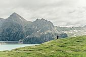 Hiker with backpack around Lünersee in Brandnertal, Vorarlberg, austria, europe.