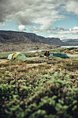 Hiker in front of two tents in greenland, greenland, arctic.