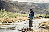 Mann angelt in der Natur Grönlands, Grönland, Arktis.