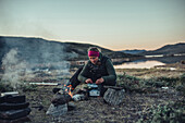 woman cooking an instant meal, greenland, arctic.