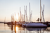 People on a jetty at the Sunset at the Ammersee lake, Bavaria, Germany, Europe