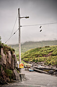 shoes attached to a power pole at small harbour, Dingle Peninsula, Slea Head Drive, County Kerry, Ireland, Wild Atlantic Way, Europe