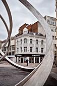 man in suit walks through historic town centre, art sculpture in foreground, Belfast, Northern Ireland, United Kingdom, Europe