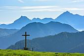 Crucifix standing on meadow, Breitenstein and Wendelstein in background, Kreuzbergalm, Gindelalmschneid, Bavarian Alps, Upper Bavaria, Bavaria, Germany