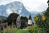 Nun at the Antonius cupel in the Kaiser valley, Kaiser mountains over Kufstein, Tyrol, Austria