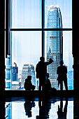 A group of visitors in the Central Plaza high-rise building overlooks the Two International Finance Centre skyscraper on Hong Kong Island, Hong Kong, China, Asia