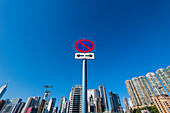 A no stopping sign in front of the skyline of high-rise buildings at Happy Valley Racecourse, Hong Kong, China, Asia