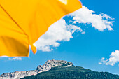 View past a yellow sunshade to the Weisshorn with the adjacent Bletterbach UNESCO World Heritage, Aldein, South Tyrol, Alto Adige, Italy
