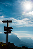 A signpost at the Tierser Alp Hut after sunrise with a view of the Plattkofel region, Siusi, South Tyrol, Alto Adige, Italy