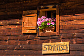 Signpost to a regulars' table at a mountain hut with geraniums in the window, Compatsch, South Tyrol, Alto Adige, Italy