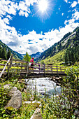 A hiker crosses a bridge with a mountain stream at the beginning of the high valley on the way to the Maxhütte, Ginzling, Zillertal, Tirol, Austria