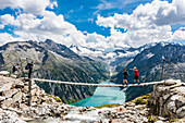Hiker  on a suspension bridge above the mountain hut Olpererhütte in front of the panorama of the Zillertal Alps with the reservoir Schlegeisspeicher, Schlegeisspeicher, Ginzling, Zillertal, Tyrol, Austria