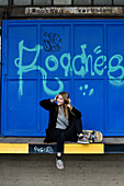 Girl with headphones and skateboard sitting in front of graffitti wall, Hamburg, Germany