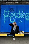 Mädchen mit Kopfhörer und Skateboard vor Graffitti Wand, Hamburg, Deutschland