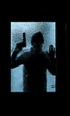 Silhouette of man holding gun looking through house window.