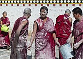 Tibetan monks enjoying a water fight after the yearly renovation of the Rongwo monastery, Tongren County, Longwu, China.